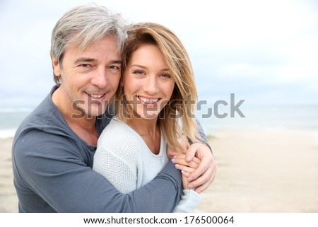 Cheerful mature couple embracing by the beach - stock photo