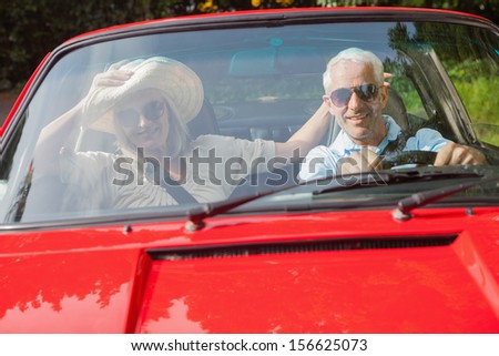 Cheerful mature couple in red cabriolet going for a ride on sunny day