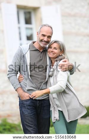 Cheerful mature couple walking in garden - stock photo