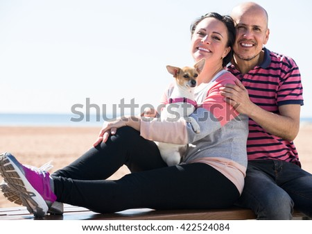 Cheerful mature couple with a small dog smiling and holding each other at the beach