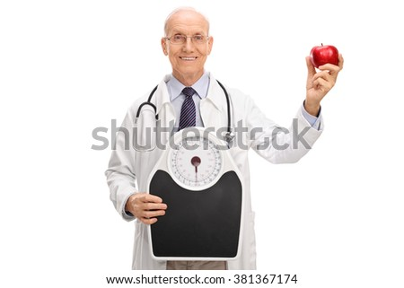 Cheerful mature doctor holding a weight scale and an apple isolated on white background