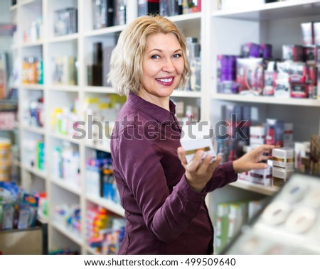 Cheerful mature european woman choosing face cream and smiling