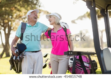 Cheerful mature golfer couple with arm around while standing on field - stock photo