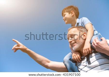 Cheerful mature grandparent is teaching his grandchild - stock photo
