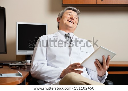 Cheerful mature male doctor holding digital tablet while sitting by desk in clinic - stock photo