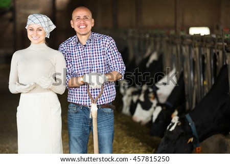 Cheerful mature man and young woman farmers standing together in cowshed  - stock photo