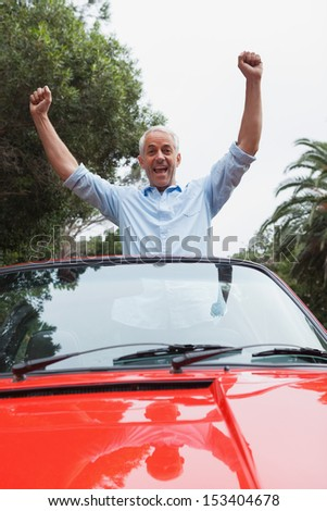 Cheerful mature man enjoying his red convertible on a bright day - stock photo