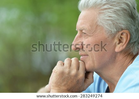cheerful mature man on walk on the nature of the spring - stock photo