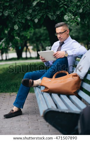 Cheerful mature man reading something on his note pad outdoor