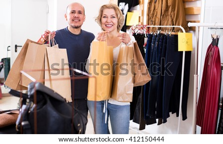 Cheerful mature spouses carrying bags with purchases in clothing store