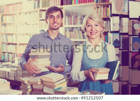 cheerful mature woman and young man carrying books in hands in book shop