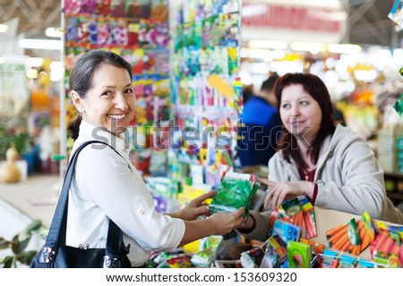 cheerful mature woman buys seeds in gardenmarket - stock photo