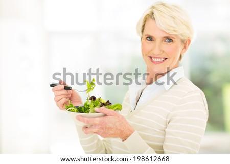 cheerful mature woman having green salad - stock photo