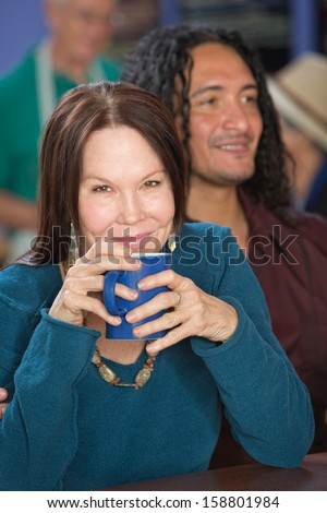 Cheerful mature woman in cafe with handsome male friend - stock photo