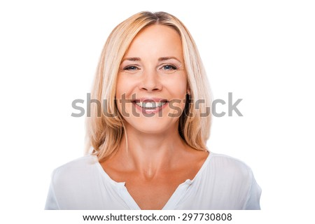 Cheerful mature woman. Portrait of happy mature woman looking at camera and smiling while standing against white background - stock photo
