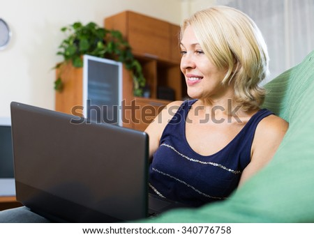 cheerful mature woman using a laptop in home