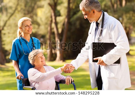 cheerful medical doctor handshaking with senior patient outdoors - stock photo