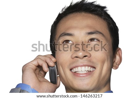 Cheerful mid-adult businessman using cell phone against white background