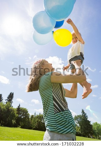 Cheerful mid adult mother and daughter playing with balloons against cloudy sky - stock photo