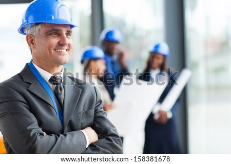 cheerful middle aged architect with arms folded