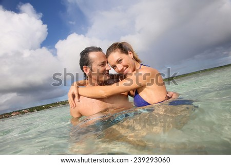 Cheerful middle-aged couple embracing in the sea - stock photo
