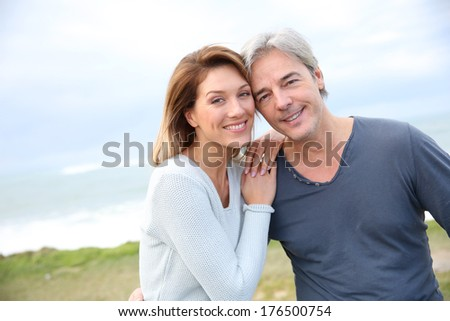 Cheerful middle-aged couple on the ocean coastline - stock photo