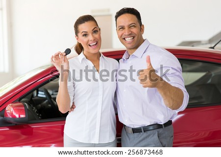 cheerful middle aged couple showing their new car key at dealership - stock photo