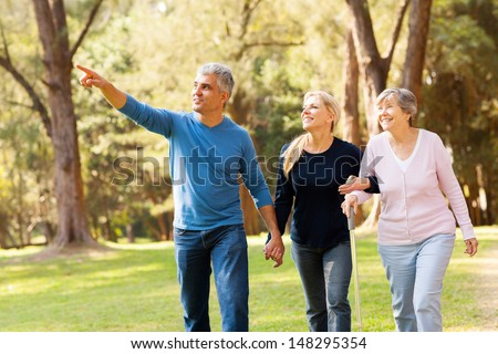 cheerful middle aged couple taking elderly mother for a walk in forest - stock photo