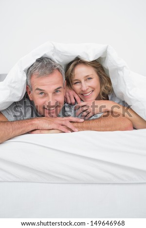 Cheerful middle aged couple under the duvet smiling at camera in bedroom at home