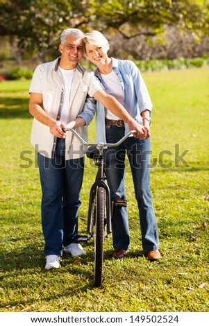 cheerful middle aged couple walking a bike at countryside