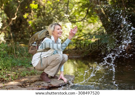 cheerful middle aged female hiker playing with stream water - stock photo