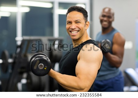 cheerful middle aged man lifting weights in gym - stock photo