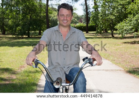 cheerful middle aged man on a bike outdoors