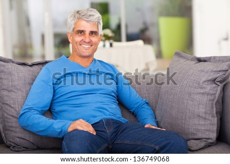 cheerful middle aged man relaxing on sofa at home - stock photo