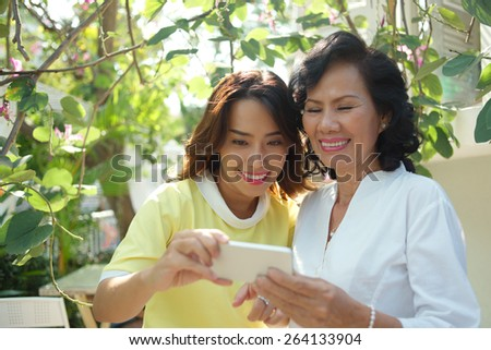 Cheerful middle-aged woman and her adult daughter looking at the photo on smartphone - stock photo