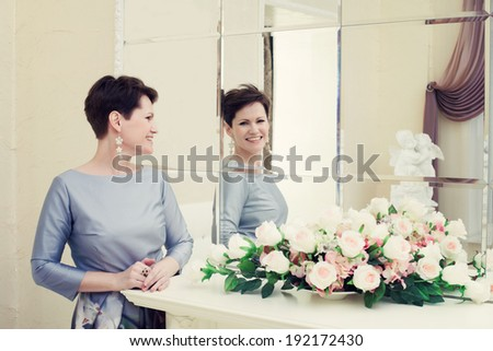 Cheerful middle aged woman laughing in mirror - stock photo