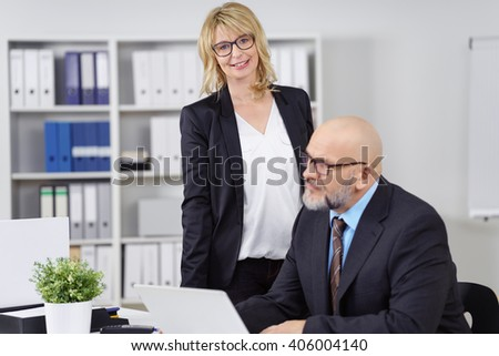 Cheerful middle aged woman standing near co-worker busy at desk with plant nearby in small business office - stock photo