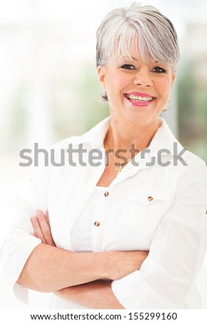 cheerful middle aged woman with arms folded - stock photo