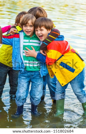 Cheerful middle school friends in rain gear  - stock photo