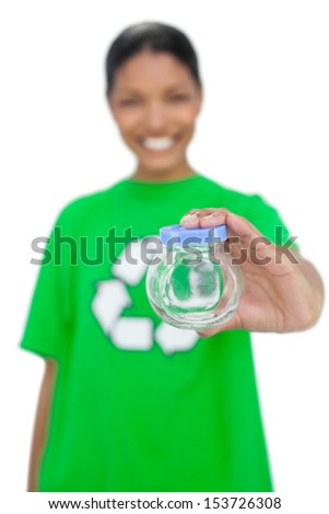 Cheerful model wearing recycling tshirt holding pot on white background - stock photo