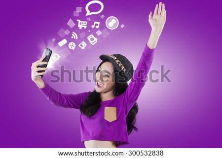 Cheerful modern teenage girl accessing internet and social media with a smartphone, shot with purple background - stock photo