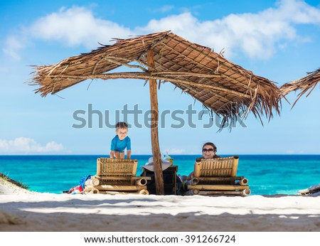 Cheerful mom and son enjoying beautiful day on the beach - stock photo