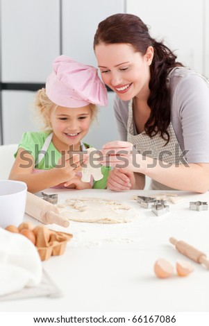 Cheerful mother and daughter making cookies in form of a man standing in the kicthen