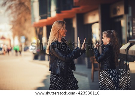 cheerful mother and daughter playing together outdoors - stock photo