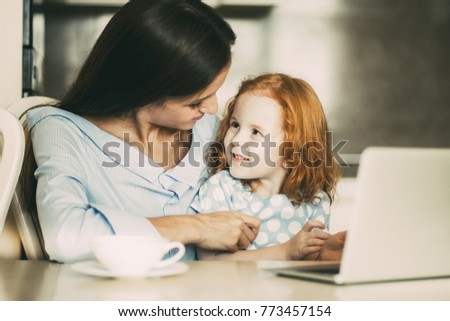 Cheerful mother and daughter sitting at laptop