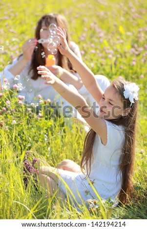 Cheerful mother and daughter sitting on green grass blow bubbles in the park in the sunshine - stock photo