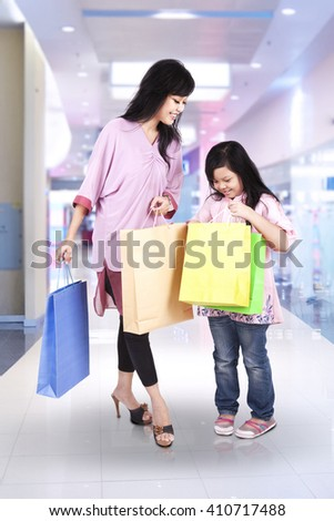 Cheerful mother and her daughter carrying shopping bags in the mall - stock photo
