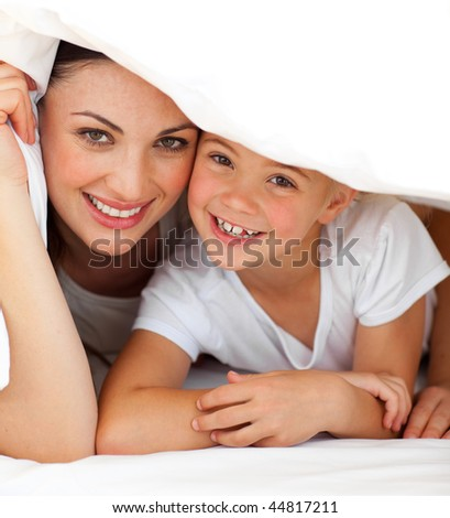Cheerful mother and her little girl playing together on a bed at home - stock photo