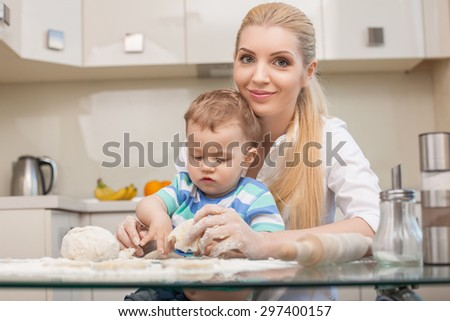 Cheerful mother and her small son are making dough with flour. They are sitting at the table. The boy is doing at it with concentration. His mom is looking at camera and smiling