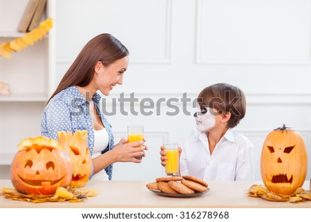 Cheerful mother and her son are having fun in Halloween. They are drinking juice and eating cookies. The woman and boy are looking at each other with joy. They are smiling - stock photo